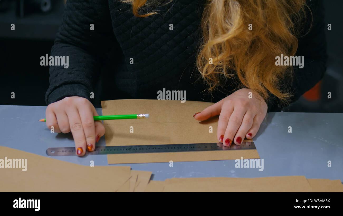Professional woman decorator, designer working with kraft paper - Stock Image
