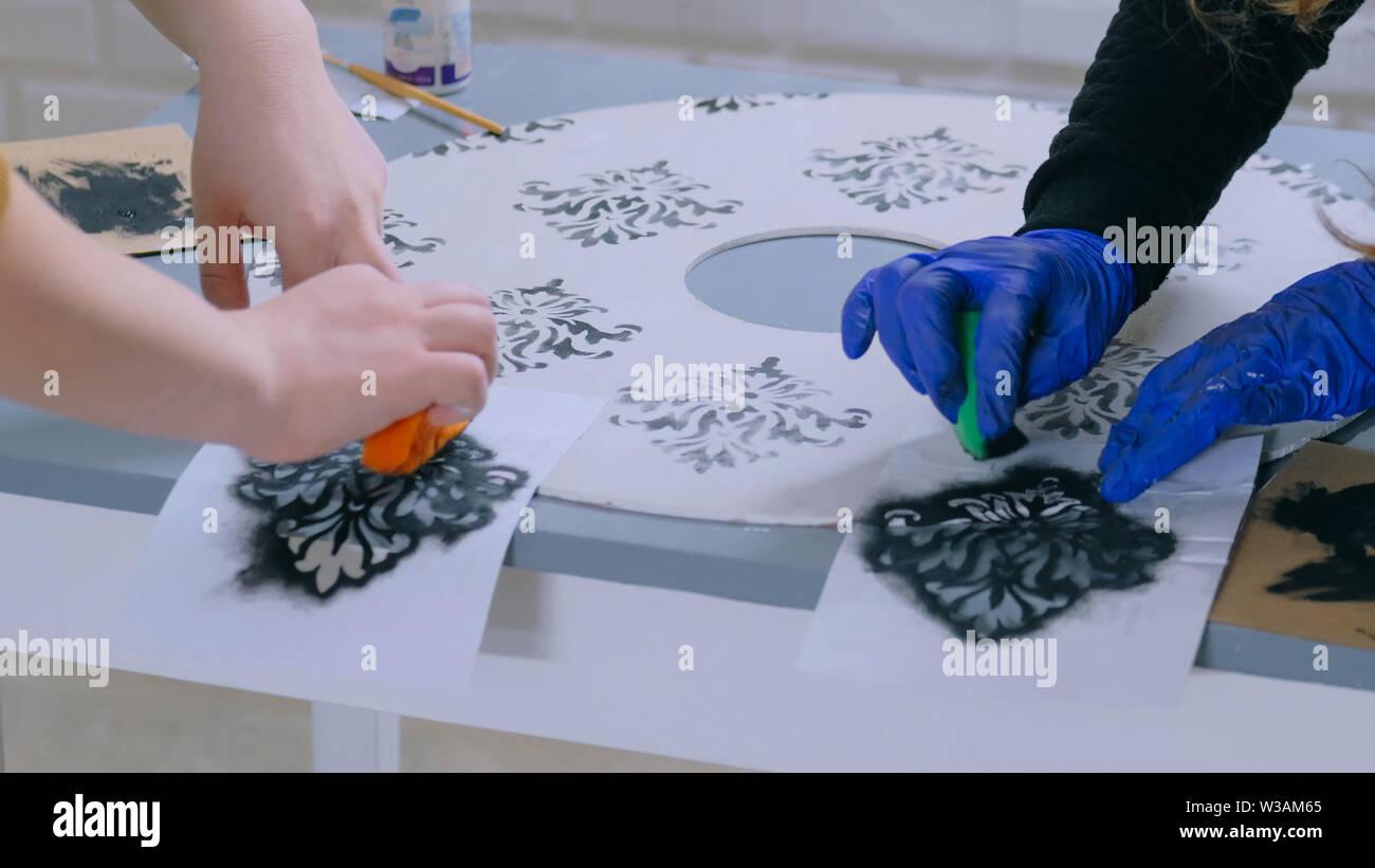 Women decorators, designers painting wooden circle decoration - Stock Image