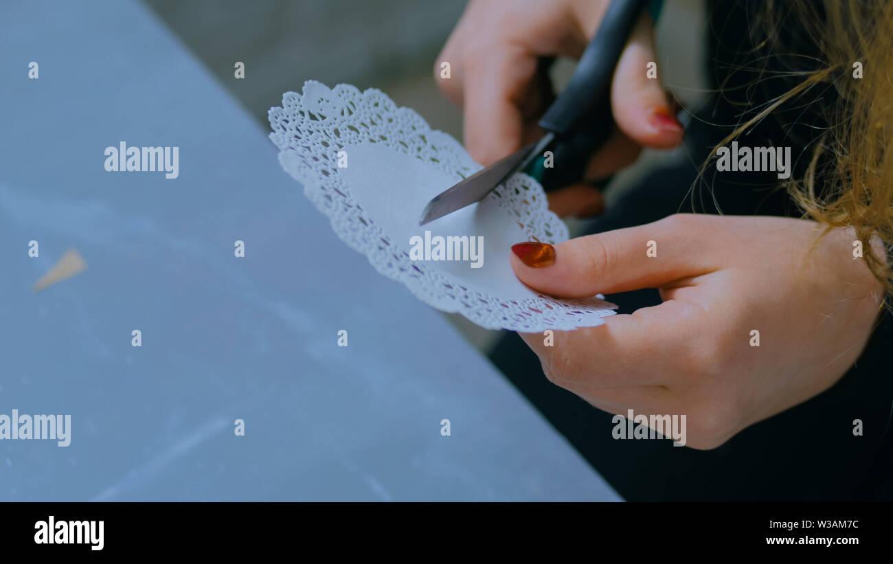 Professional woman decorator, designer cutting paper pattern - Stock Image