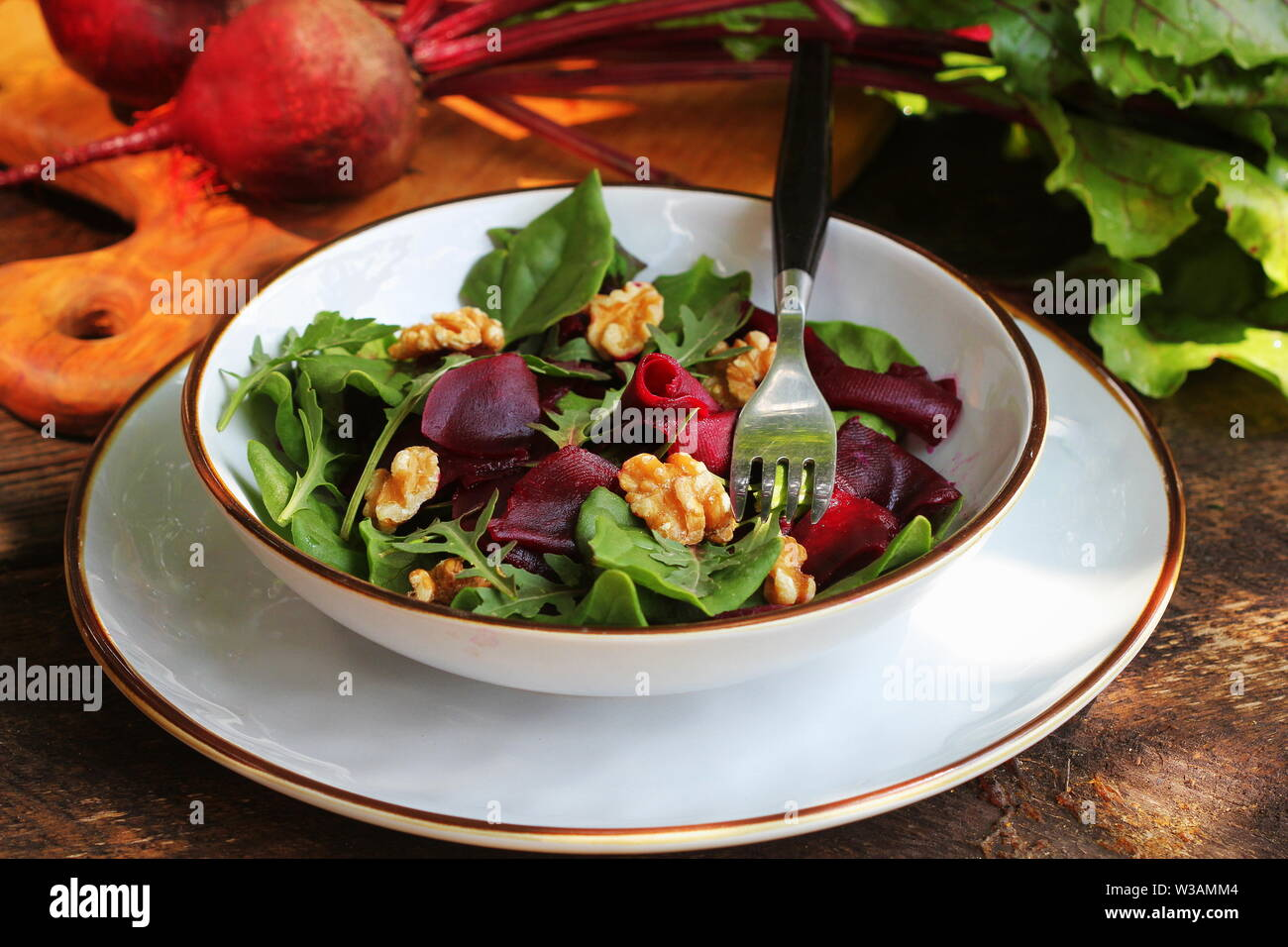 Healthy Beet Salad with fresh sweet baby spinach, arugula, nuts on wooden background Stock Photo