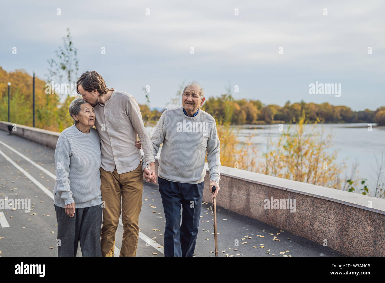 An elderly couple walks in the park with a male assistant or adult grandson. Caring for the elderly, volunteering - Stock Image