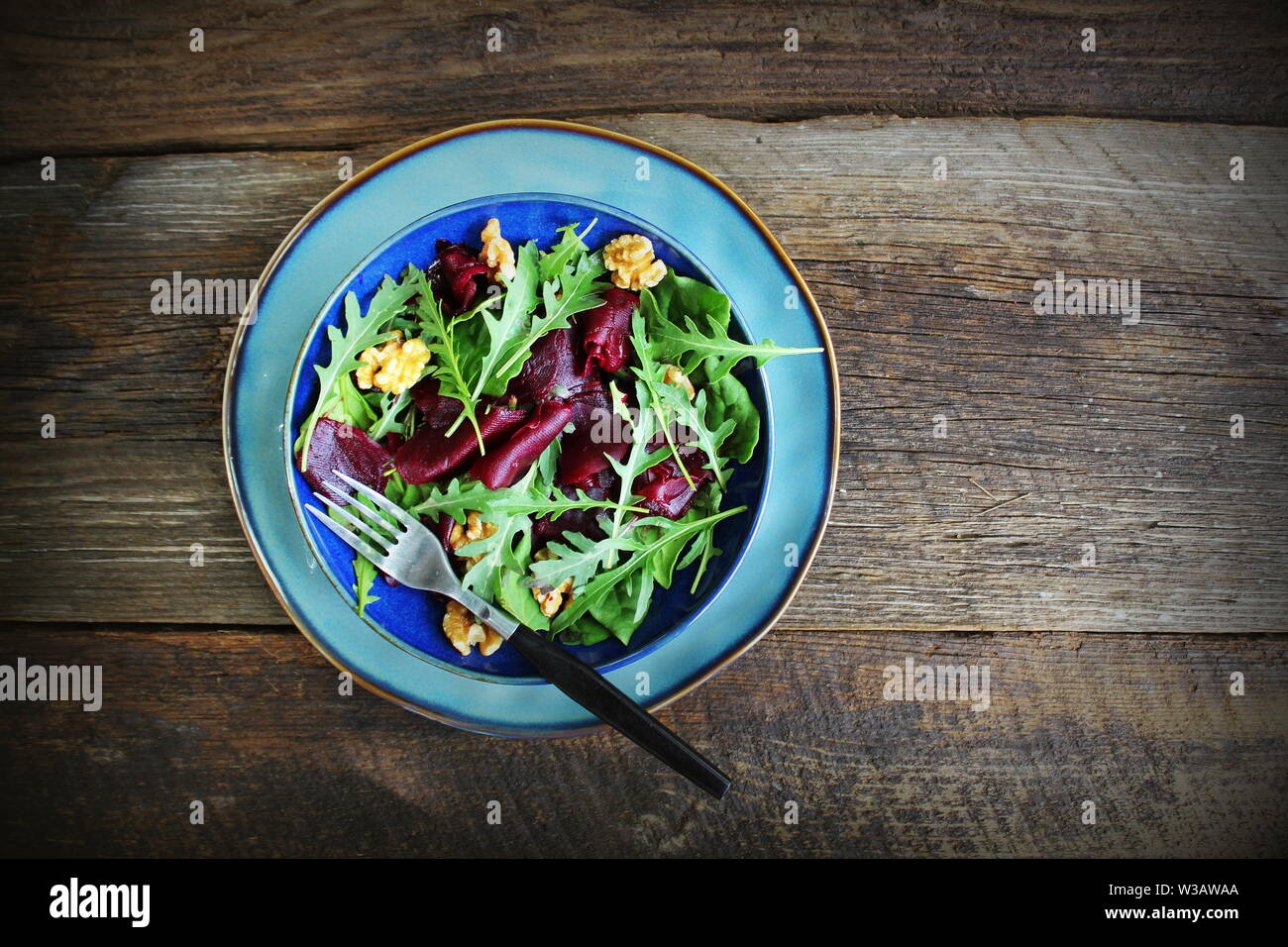 Healthy Beet Salad with fresh sweet baby spinach, arugula, nuts on wooden background . Top view Stock Photo