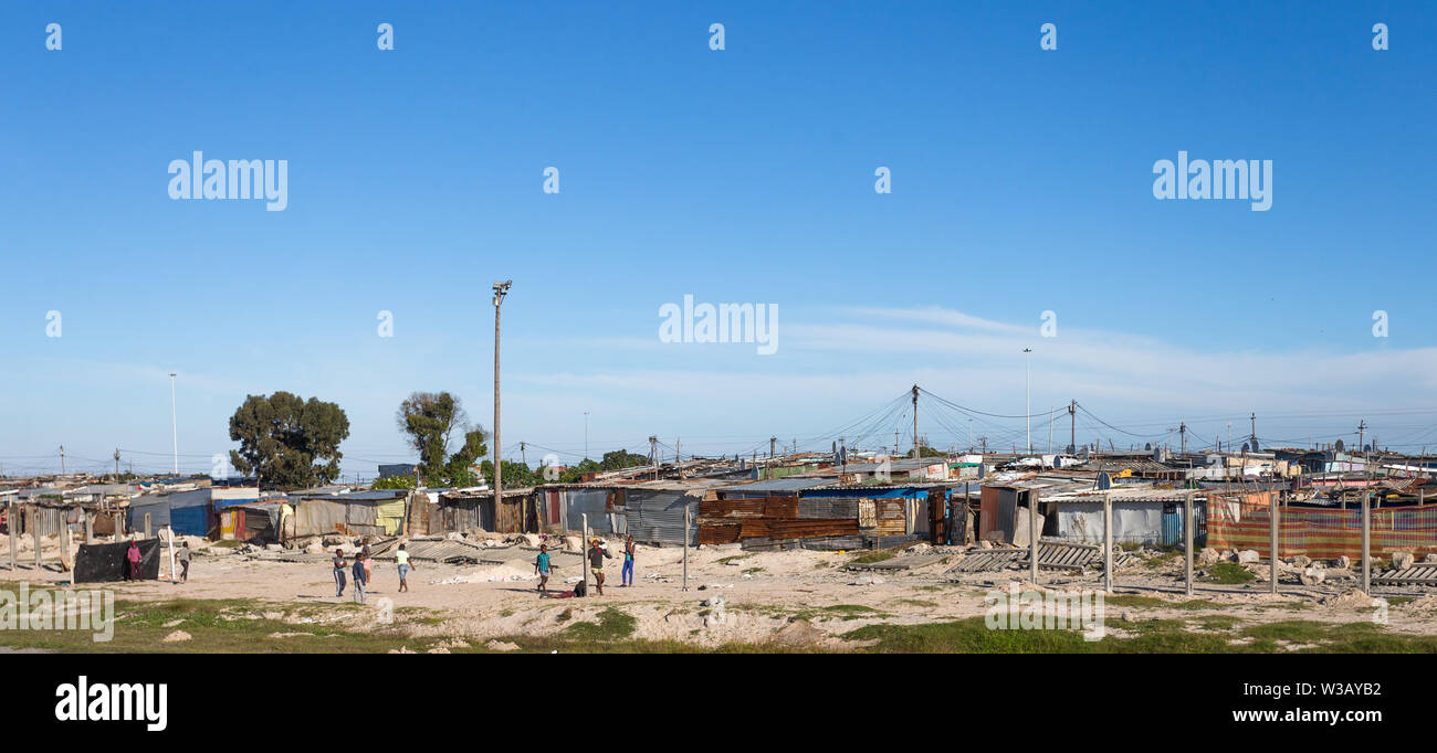 group of poor black African children playing soccer or football outside a tin shack informal settlement or squatter camp in Cape Town, South Africa Stock Photo