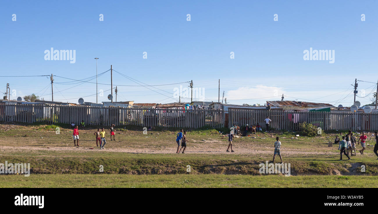 group of poor black African children playing a game of soccer or football on a grass verge in front of a fence and tin shacks Cape Town, South Africa Stock Photo