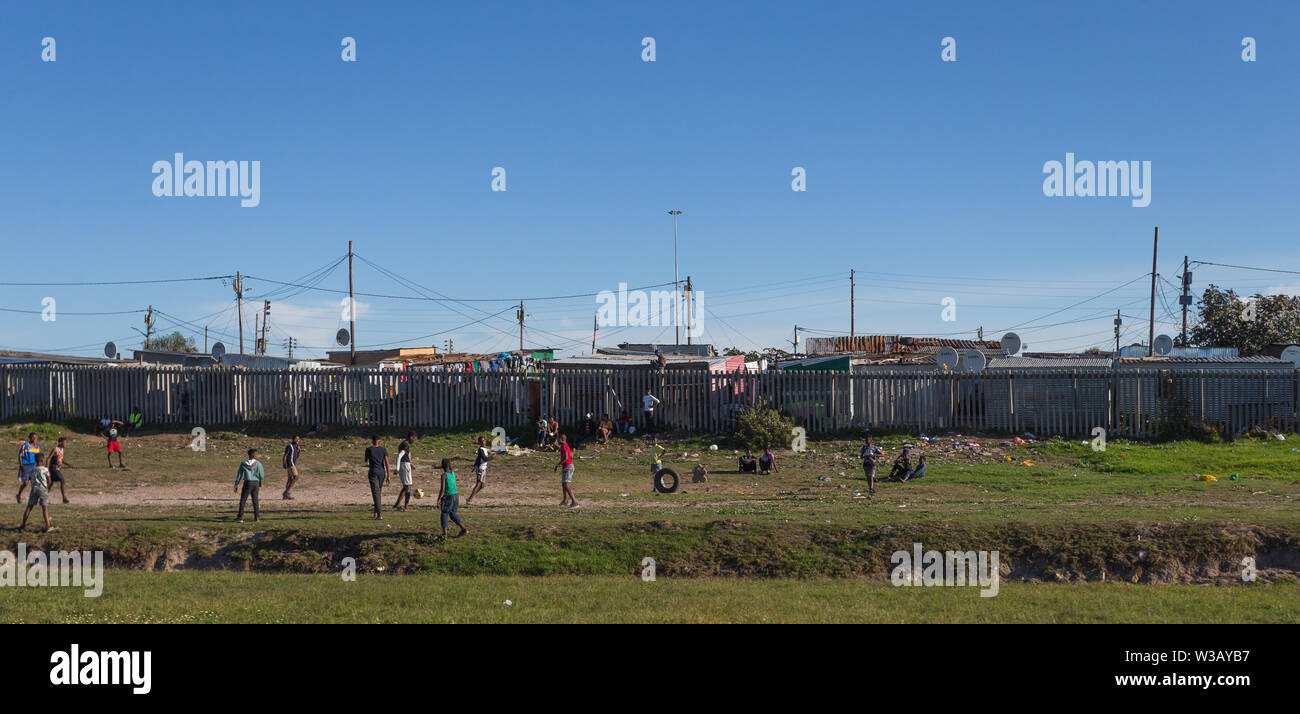 group of poor black African children playing a game of soccer or football on the side of the highway with tin shack houses in the background Cape Town Stock Photo