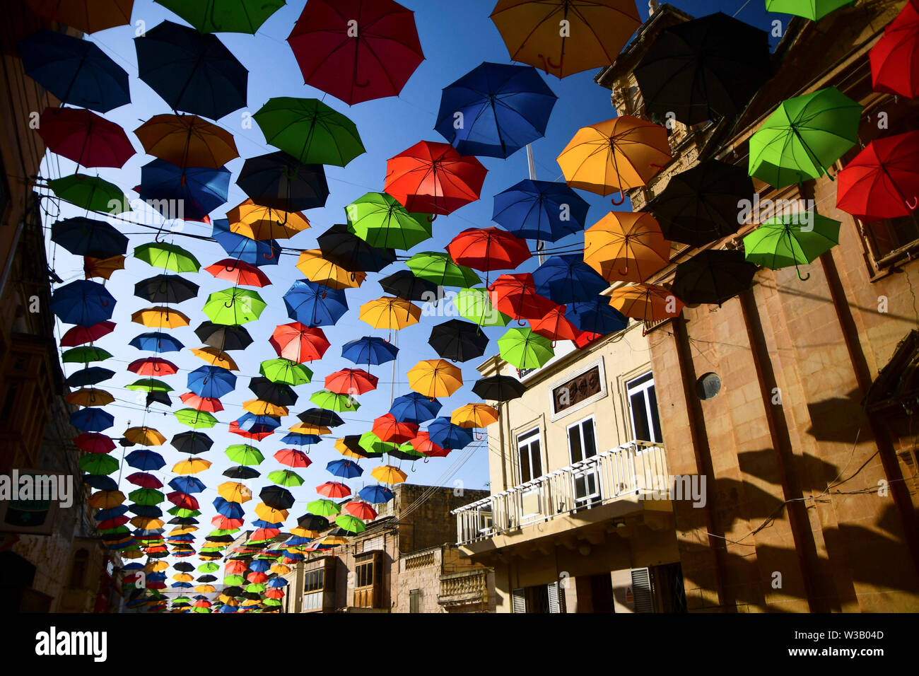 Zabbar. 13th July, 2019. Photo taken on July 13, 2019 shows umbrellas suspended in the air along a street to bring back the popular 'Umbrella Street' spectacle in Zabbar, Malta. Credit: Jonathan Borg/Xinhua/Alamy Live News - Stock Image