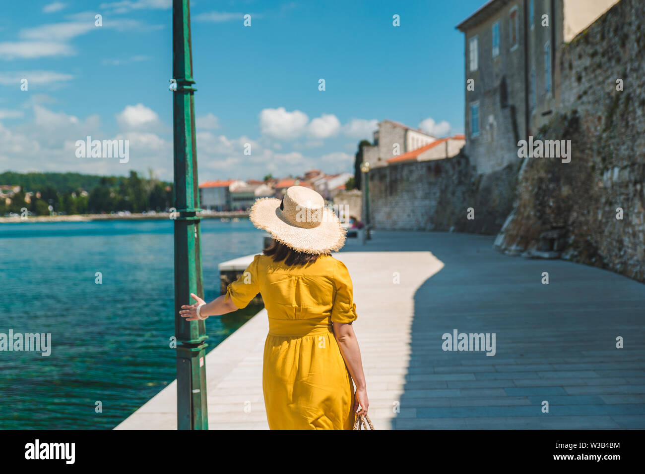 woman walking by sea quay in summer day in yellow sundress. summer vacation - Stock Image