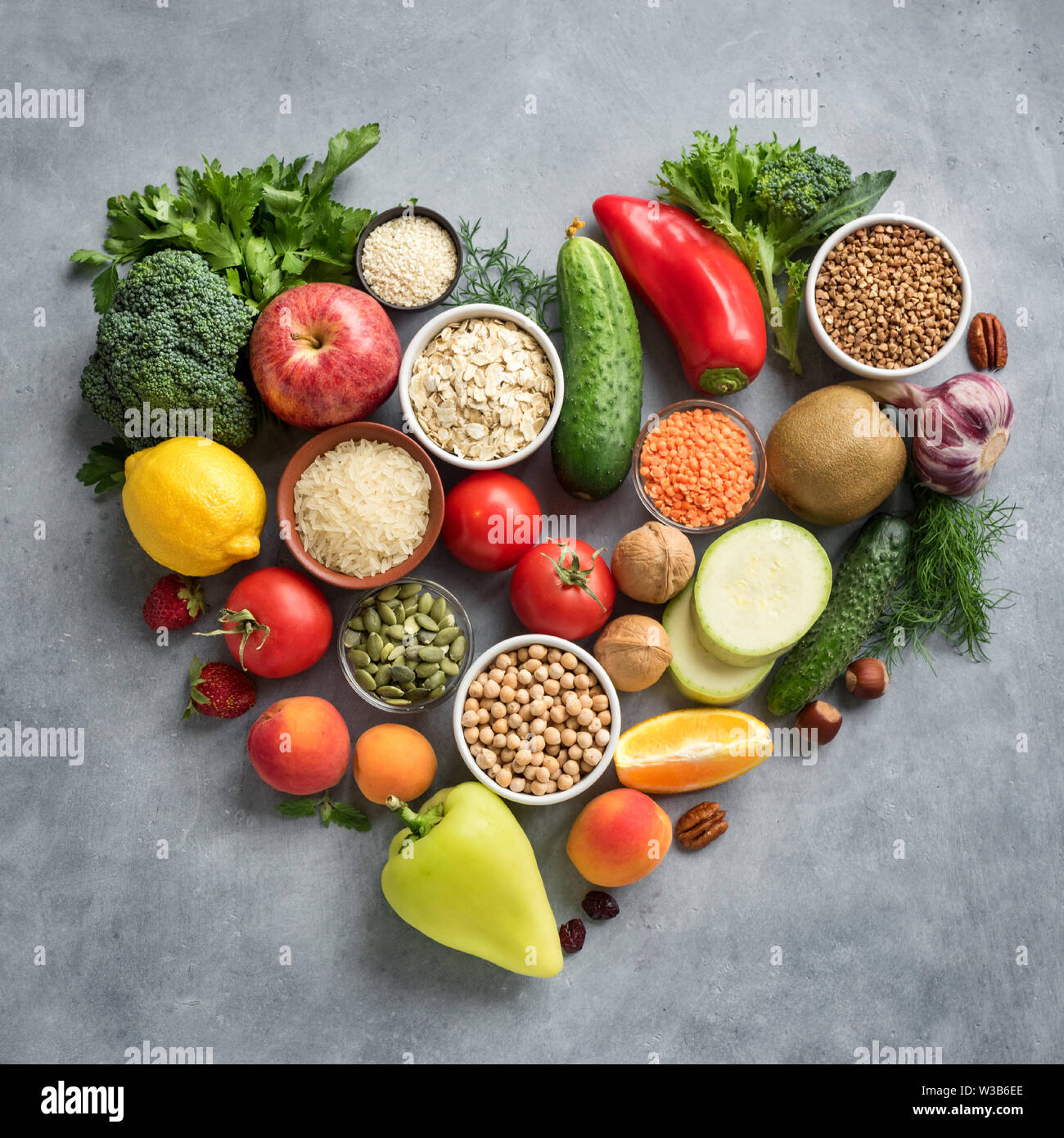 Healthy Vegan Food Background - organic food in heart shaped flat lay, top view. Healthy clean eating, diet  or detox concept. Stock Photo
