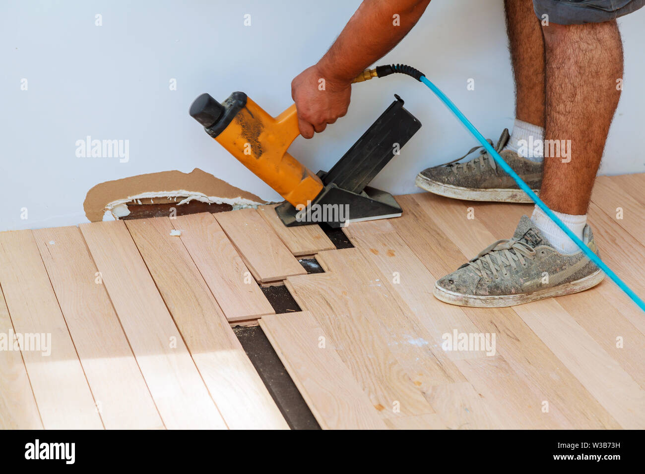 Carpenter worker installing wood parquet board during flooring work with hammer - Stock Image