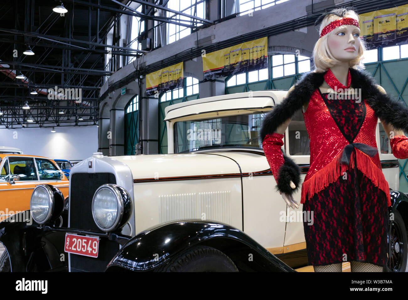 BUDAPEST, HUNGARY - April 05, 2019: Side view of a rare white 1920s classic oldtimer car, with a life size doll in period clothes beside it. - Stock Image