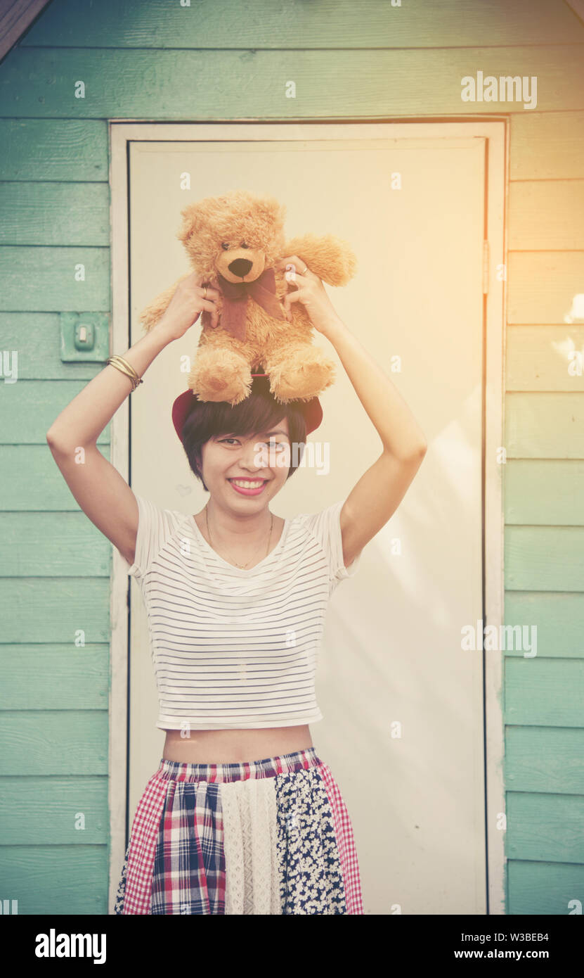 Portrait of happy female with a lovely teddy bear looking at camera. - Stock Image