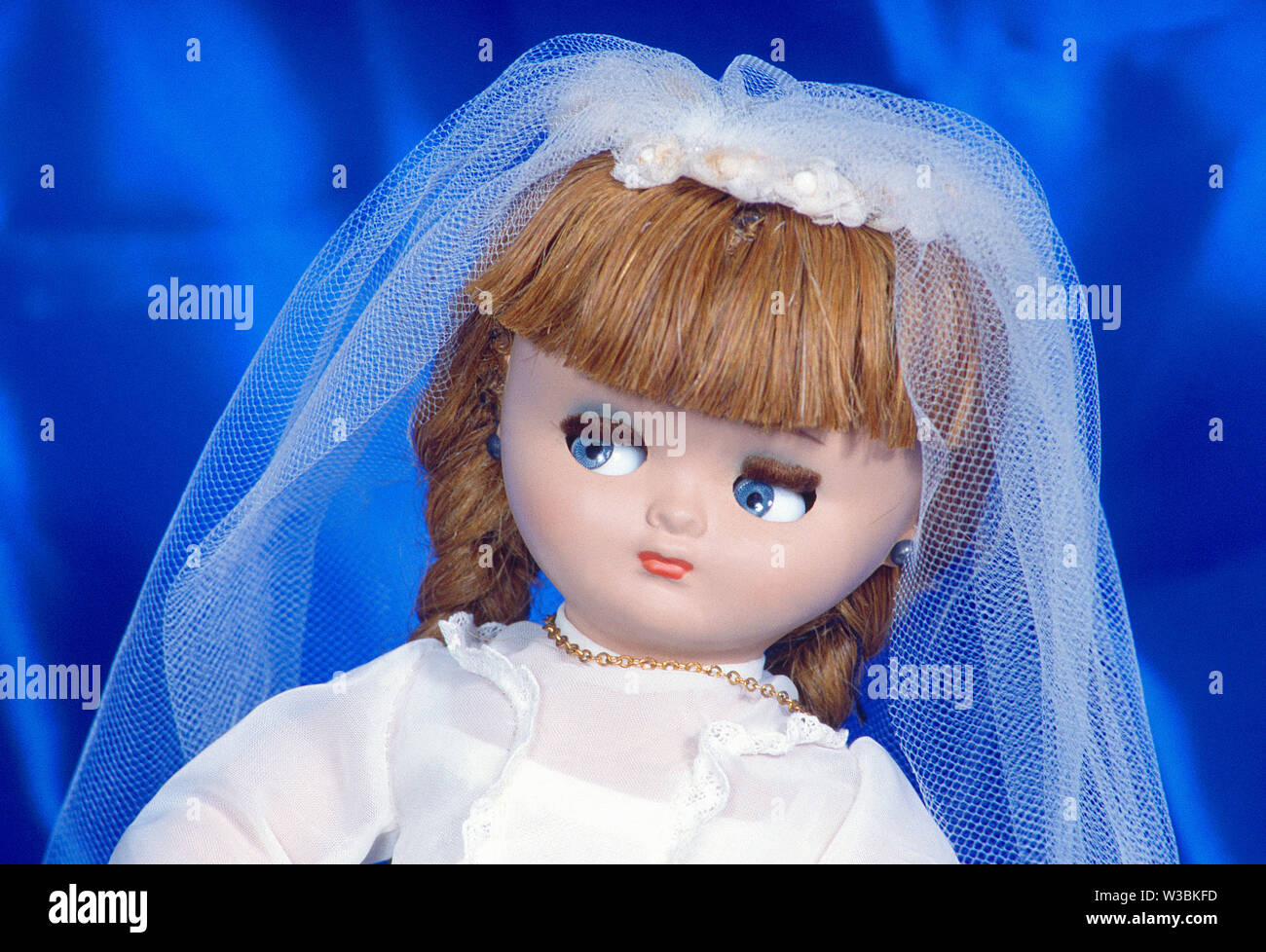 Doll wearing First Communion dress. Close view. - Stock Image