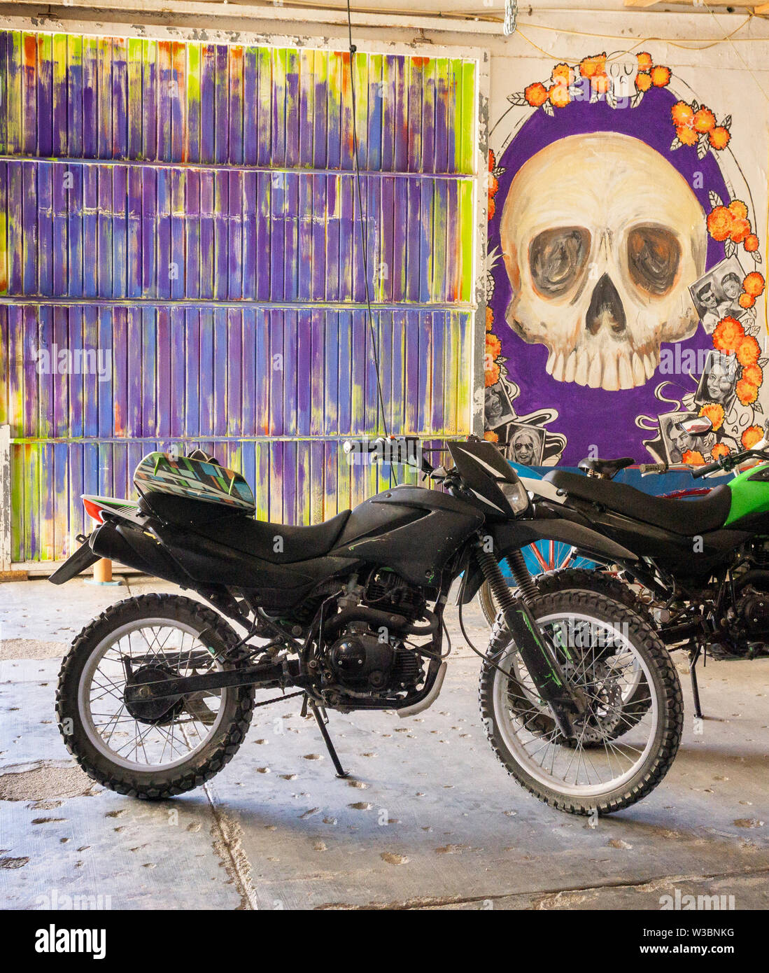 garage with a motorbike on a multicolored wall and paint of a skull - Stock Image