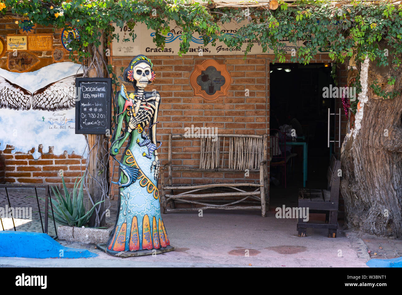 a colorful life sized doll ,representing the mexican dias del los muertos ,is standing in front of a door entrance - Stock Image