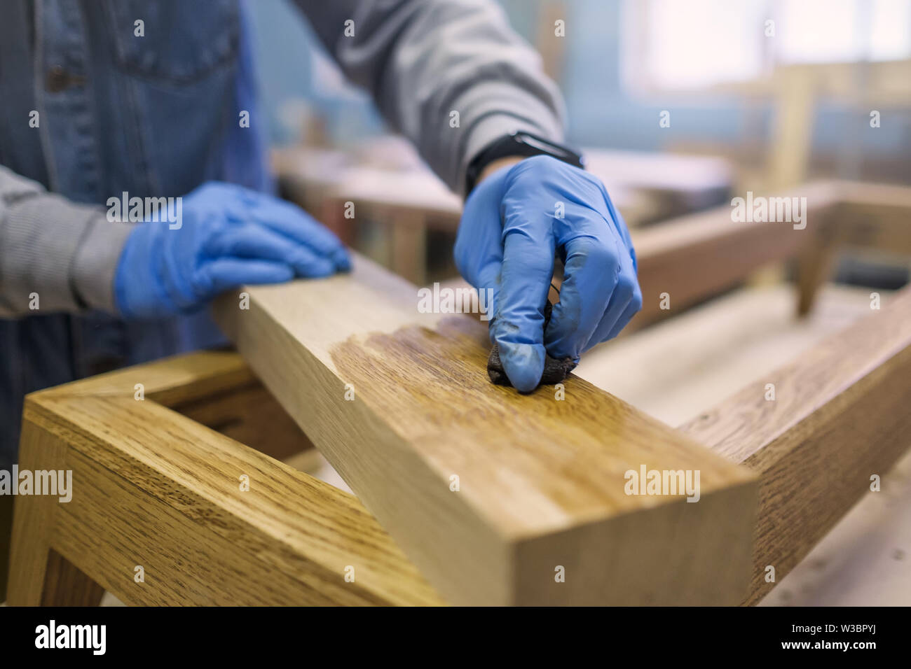 male hand paint wooden surface with brown paint - Stock Image