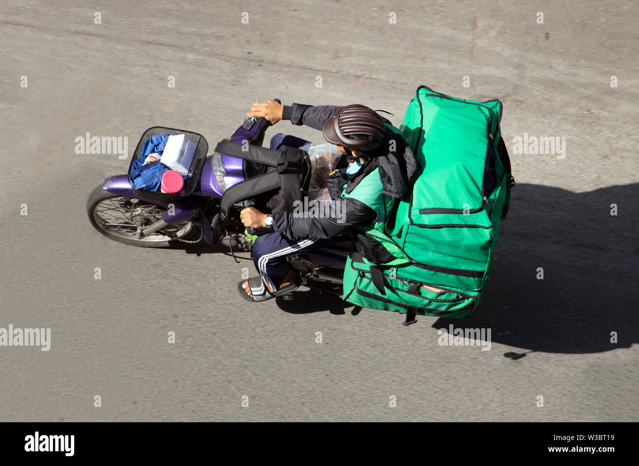 Delivery of consignments on motorbike. Motorcyclist rides with delivery in the many green bags on street Saigon city, Vietnam. - Stock Image