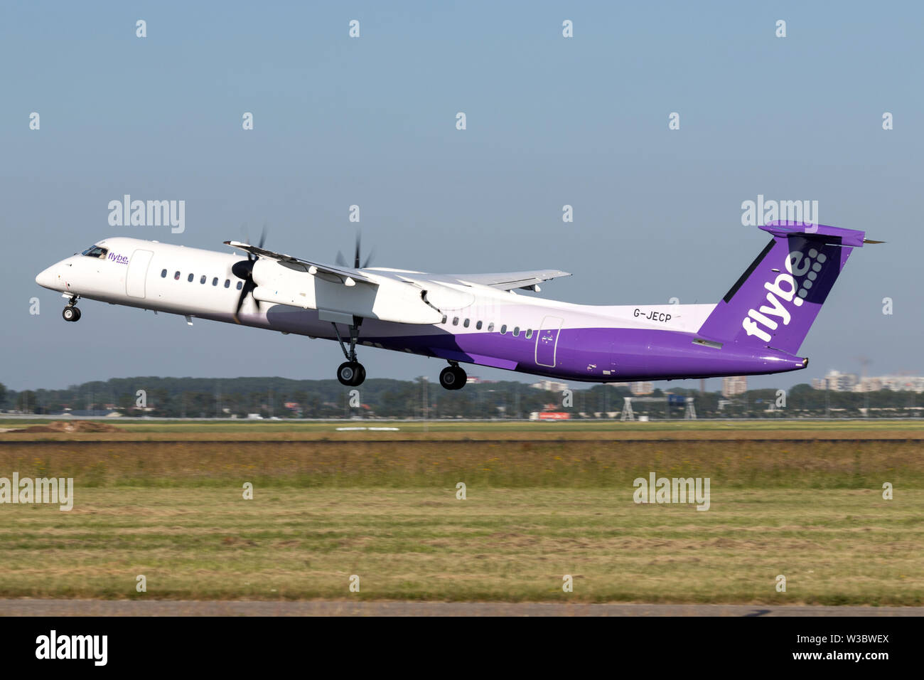 British flybe Bombardier DHC-8-400 Dash 8 with registration G-JECP taking off runway 36L (Polderbaan) of Amsterdam Airport Schiphol. - Stock Image