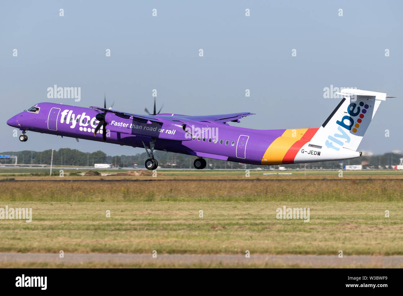 British flybe Bombardier DHC-8-400 Dash 8 with registration G-JEDW taking off runway 36L (Polderbaan) of Amsterdam Airport Schiphol. - Stock Image