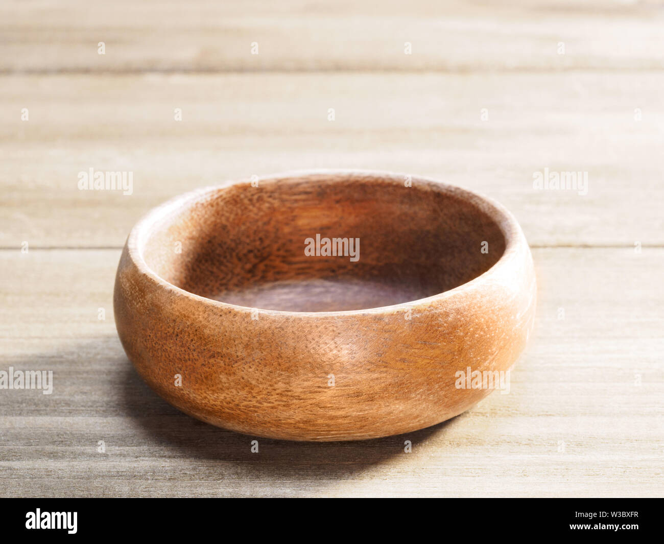 Wooden cup for cosmetic products on brown wooden background - Stock Image