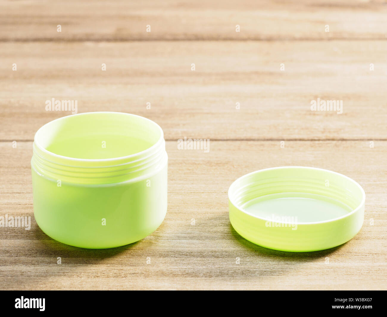 Green cup for cosmetic products with open cap isolated on wooden background - Stock Image