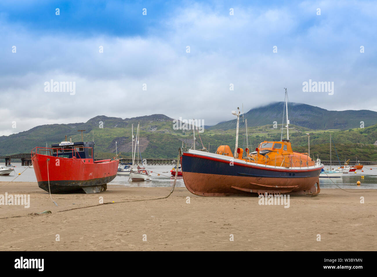 A former RNLI Watson class lifeboat sits on the sand at low water in the Mawddach estuary at Barmouth, Gwynedd, Wales, UK - Stock Image