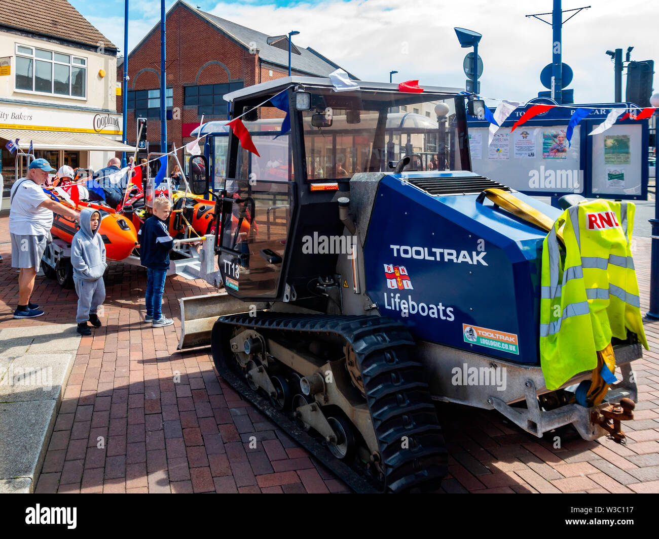 Parents and Children viewing a small RNLI inflatable lifeboat with a Tooltrak tracked launch tractor on display in Redcar High Street for fund raising - Stock Image