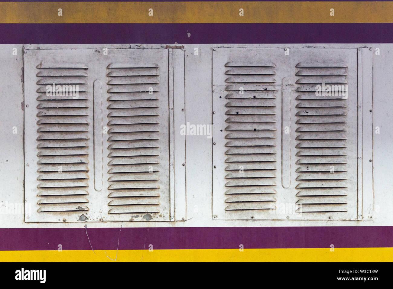 White metal windows on a carriage of a thailandese railways train - Stock Image