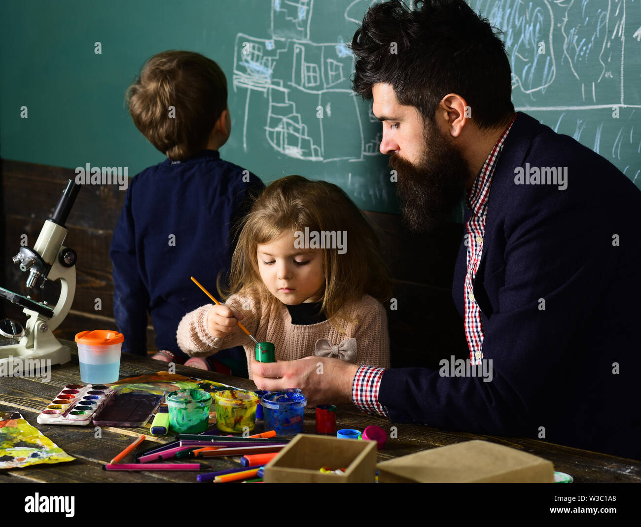 Lesson with qualified private tutor. Kids struggle when they do homework so they need tutor. Teacher helping pupil in classroom at the elementary scho - Stock Image