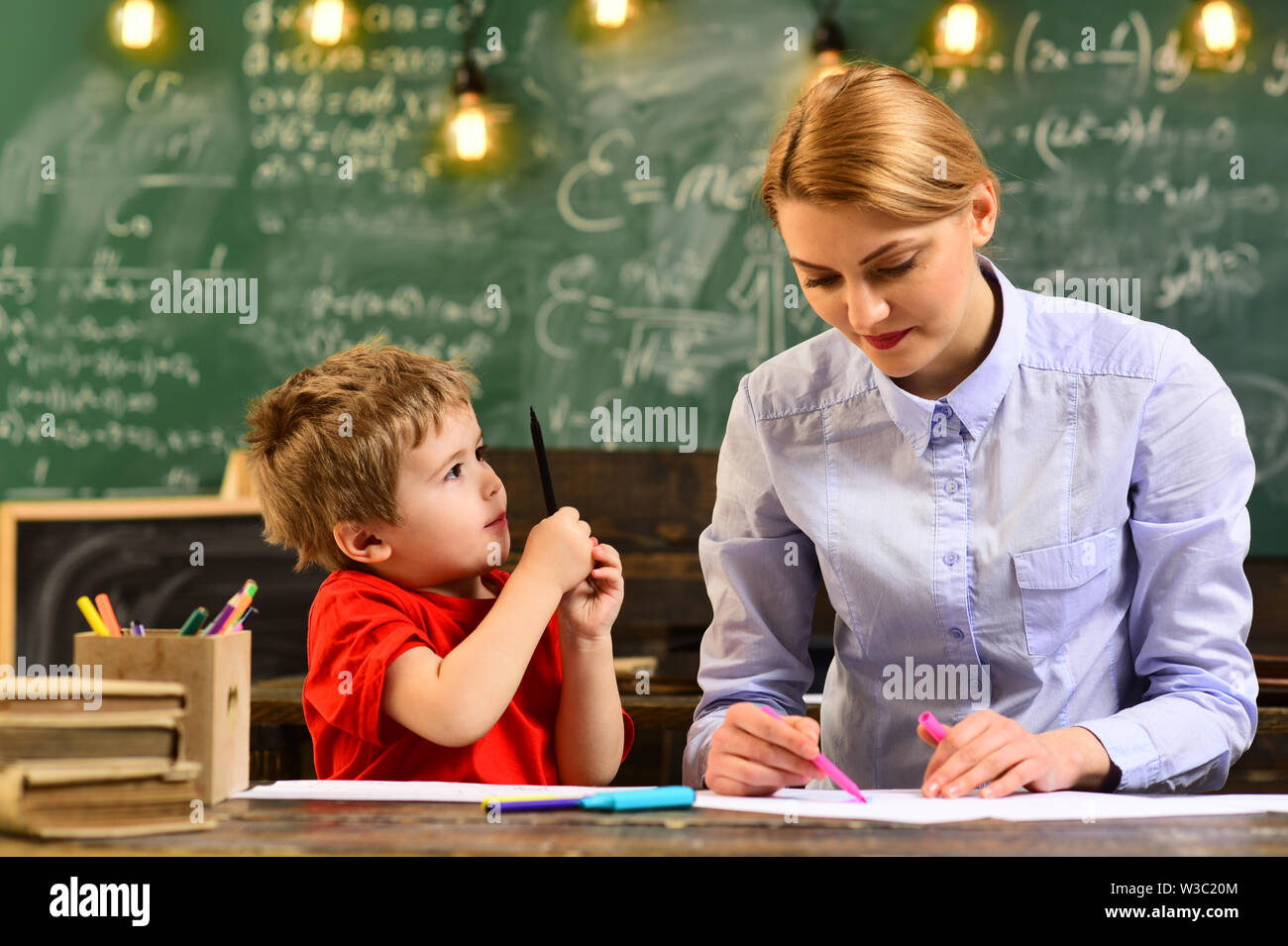 Tutor should believe that things can be changed through action, Back to school, Good teachers seek engaged students, Attentive teacher talking to her - Stock Image
