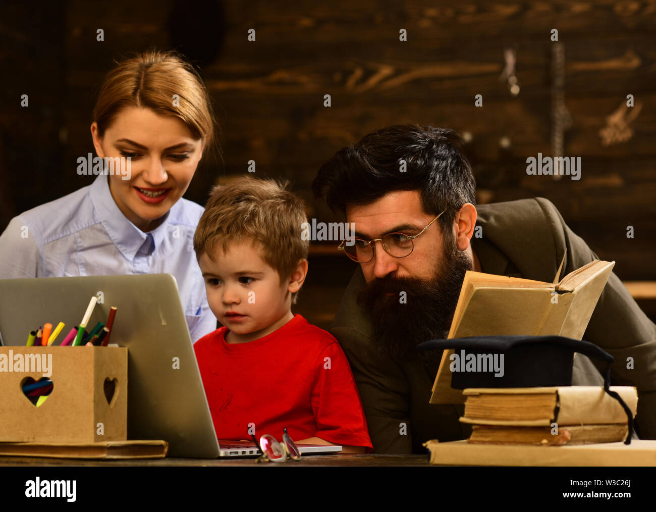 Friendly teacher and adult smiling student in classroom, Awesome teachers know about things that make students curious, Hipster is solving math exam, - Stock Image