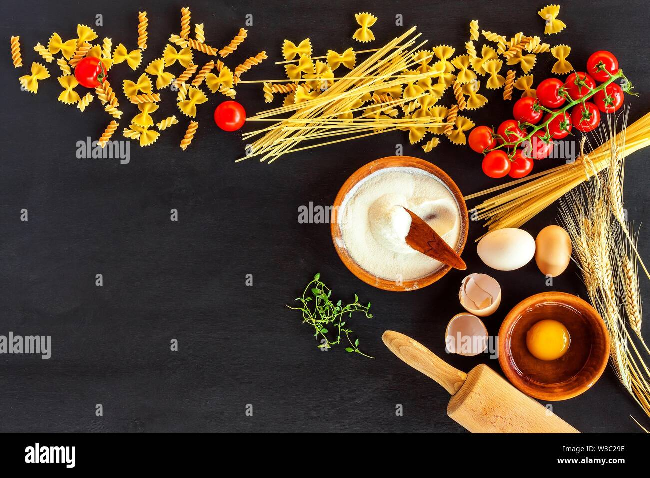 Home made traditional pasta. Flour grain egg pasta on black background. Home cooking food. - Stock Image