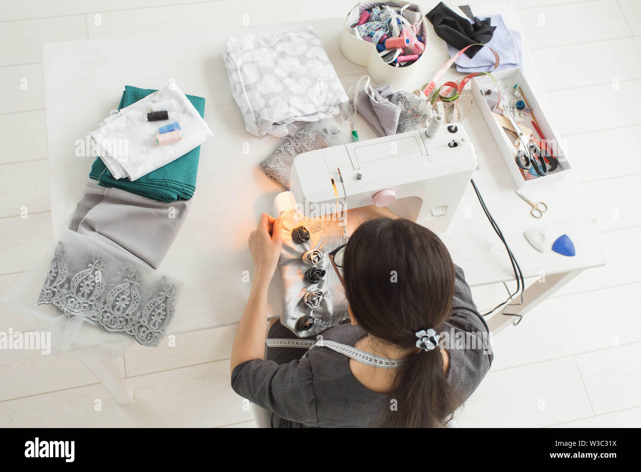 Tailor, fashion and seamstress concept - young female fashion designer in her showroom, top view - Stock Image