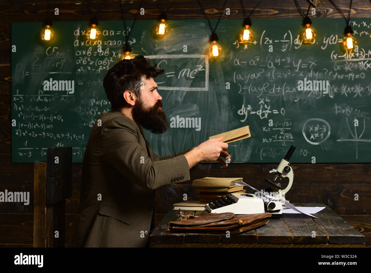 Teacher is sitting at the table in classroom, Teachers who become great or master teachers seek out the help they need, People learning education and - Stock Image