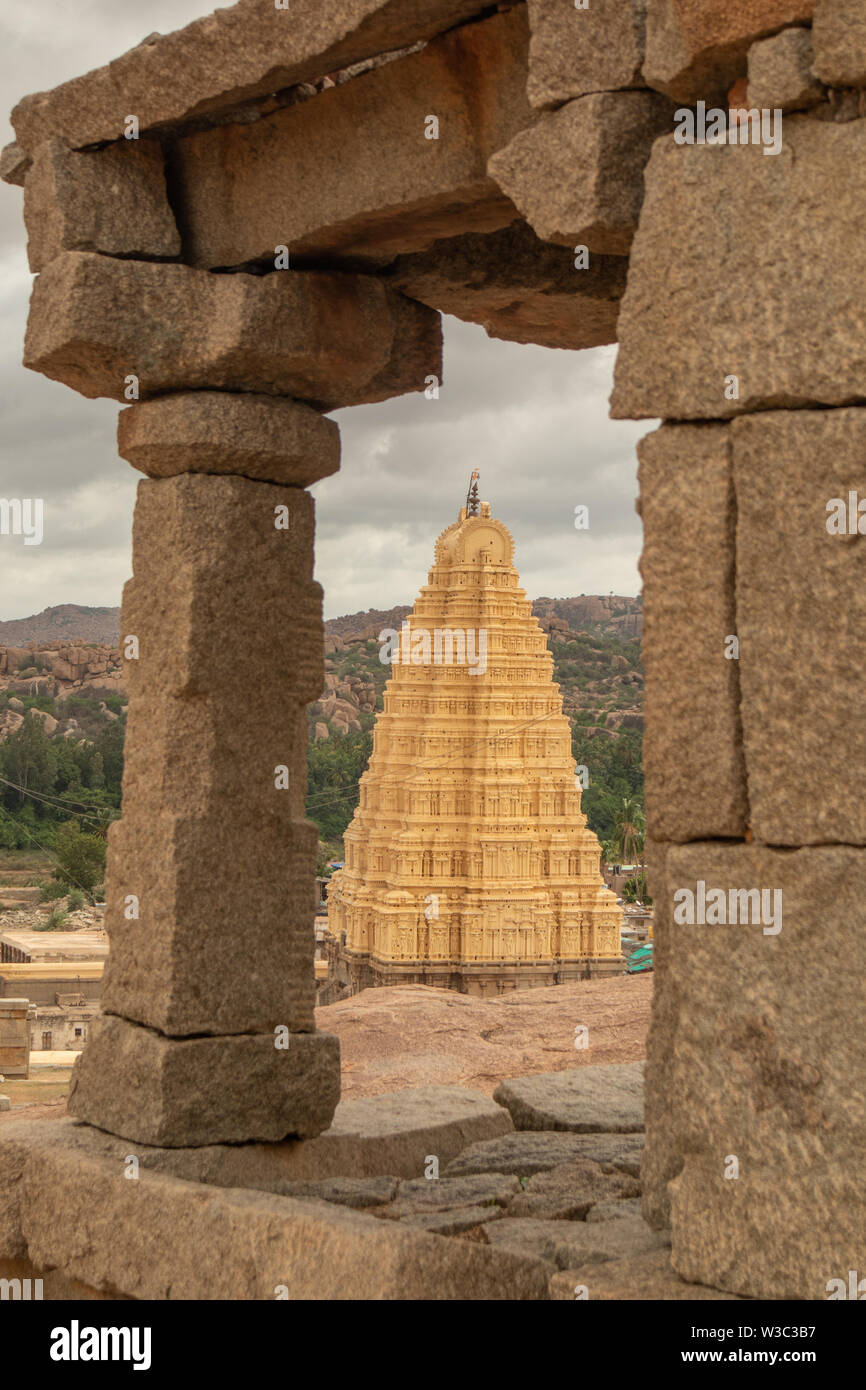 Virupaksha hindu temple gopuram through the Mandapa and ruins, Hampi, India - Stock Image