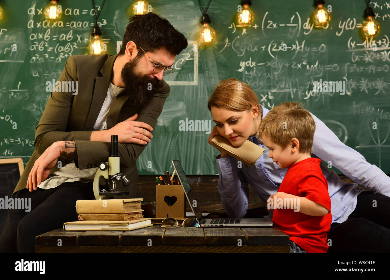 Worry student have a problem with mathematics,E-Learning concept with student holding his modern laptop computer, Teacher in glasses reading reports o - Stock Image