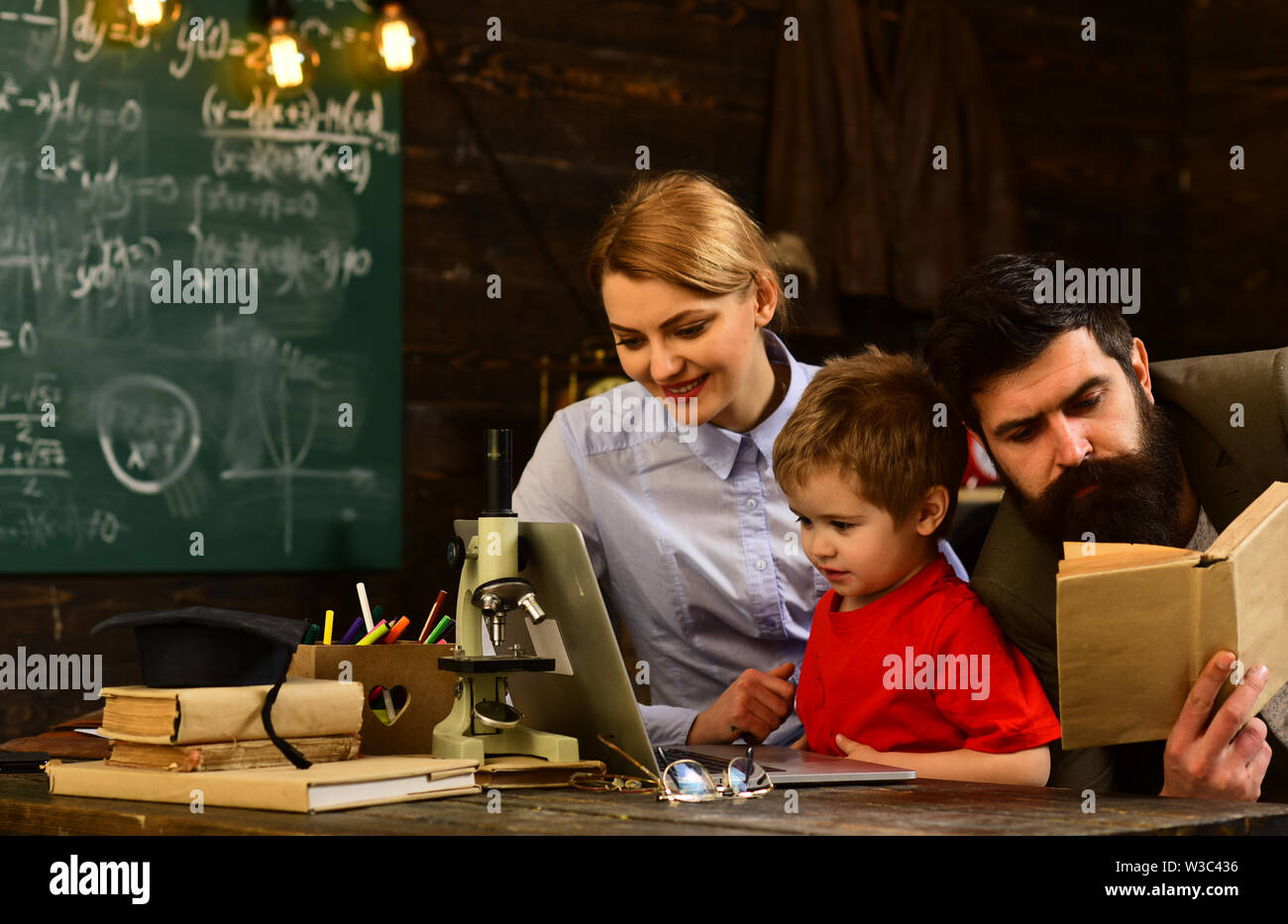 Mature tutor eacher giving private lessons to preschool boy, Teacher drawing at classroom in school, Concept education - back to school on green backg - Stock Image