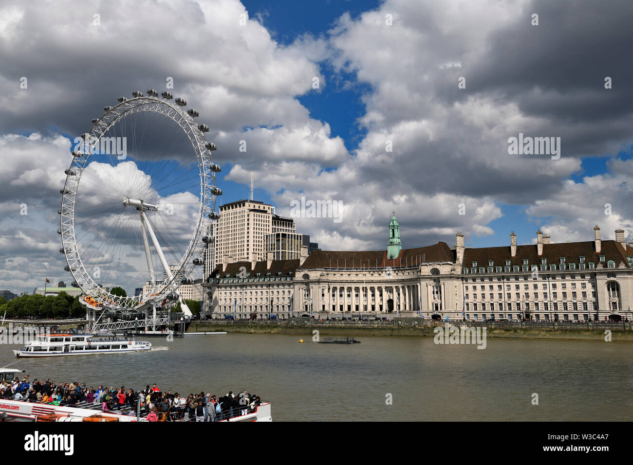 London Eye on the River Thames with tourists on tour boats and Shrek's adventure and Sea Life Centre Aquarium London England - Stock Image