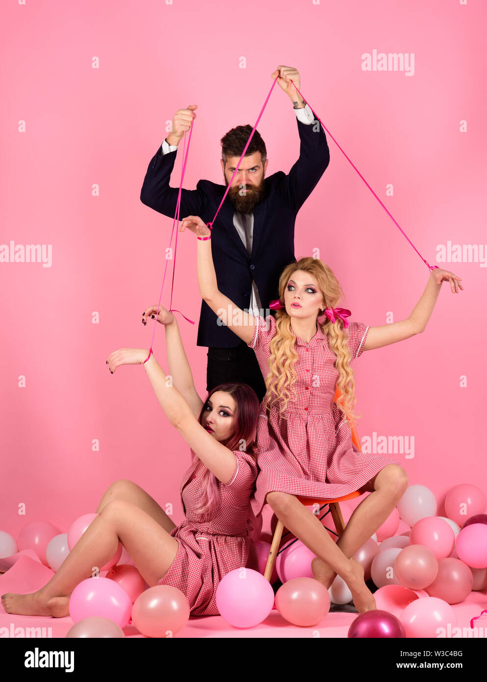 Creative idea. Love triangle. vintage fashion women puppet and man. retro girls and master in party balloons. Crazy girls and man on pink. Halloween. - Stock Image