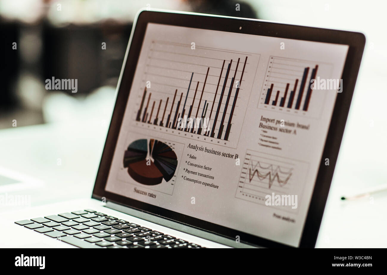 closeup of the laptop screen with financial chart on a workplace of the businessman - Stock Image