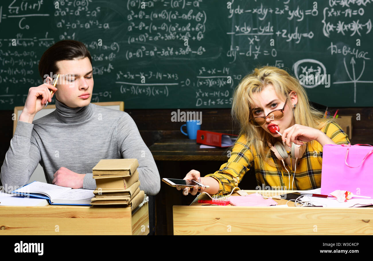 Final exam test in university students study for examination in classroom. High school college students studying and reading together in class educati - Stock Image