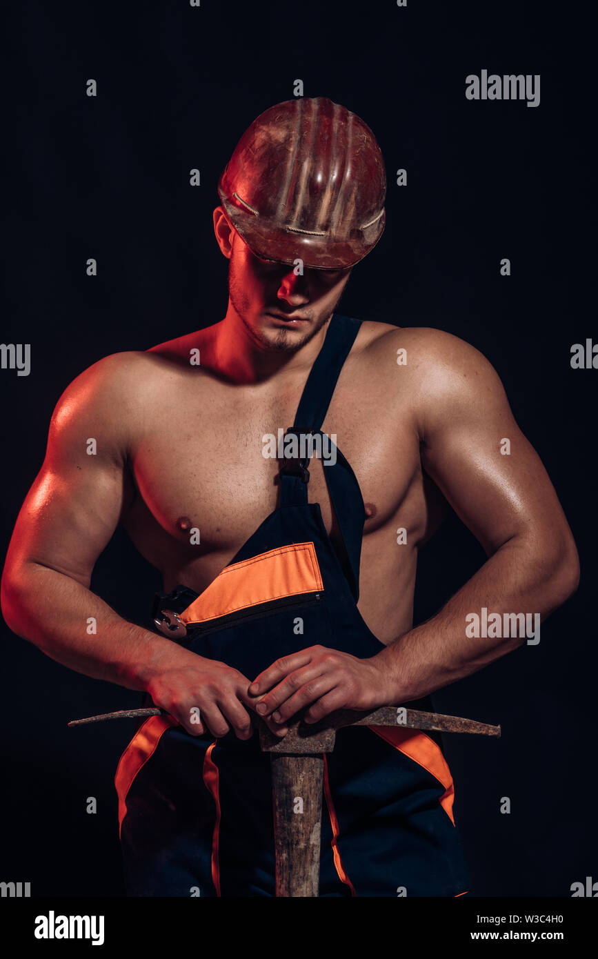 Mining area under construction. Man miner with mining equipment. Muscular man worker. Hard worker with muscular torso. Construction worker. Under cons - Stock Image
