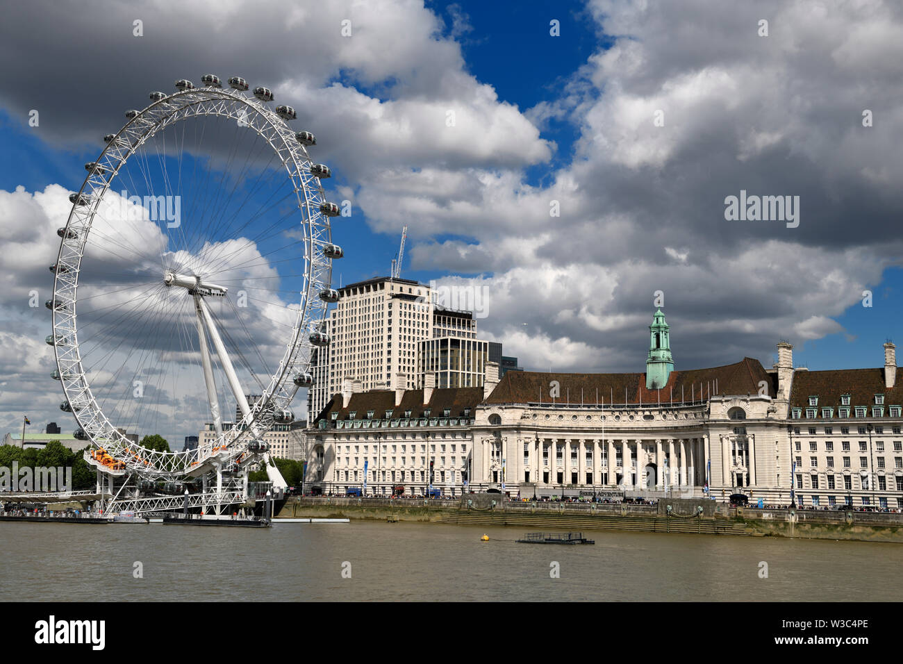 London Eye on the River Thames with tourists lined up at Shrek's adventure and Sea Life Centre Aquarium London England - Stock Image