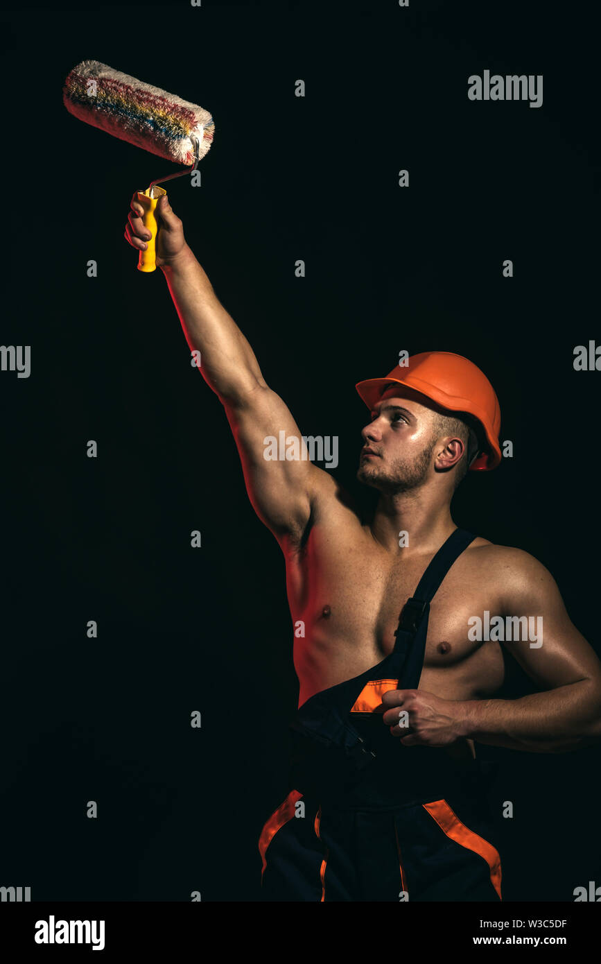 The perfect paint job. Skilled painter or decorator man. Construction worker or builder. Muscular man at painting work. Worker hold brush roller in mu - Stock Image