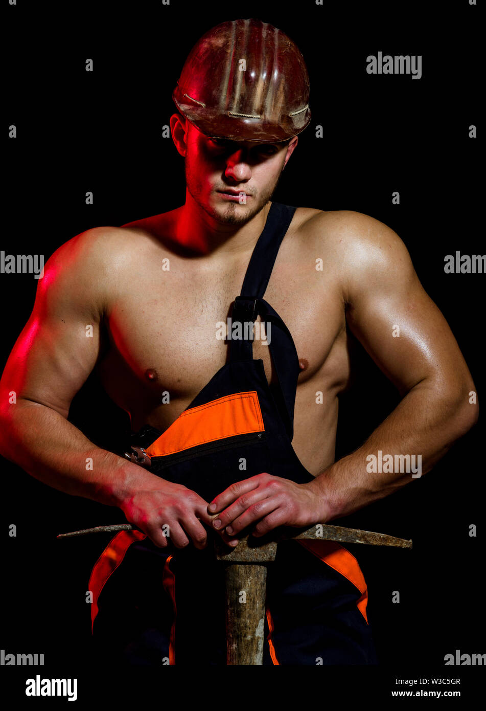 Under construction, we are closed for refurbishment. Muscular man worker. Hard worker with muscular torso. Construction worker. Man miner with mining - Stock Image