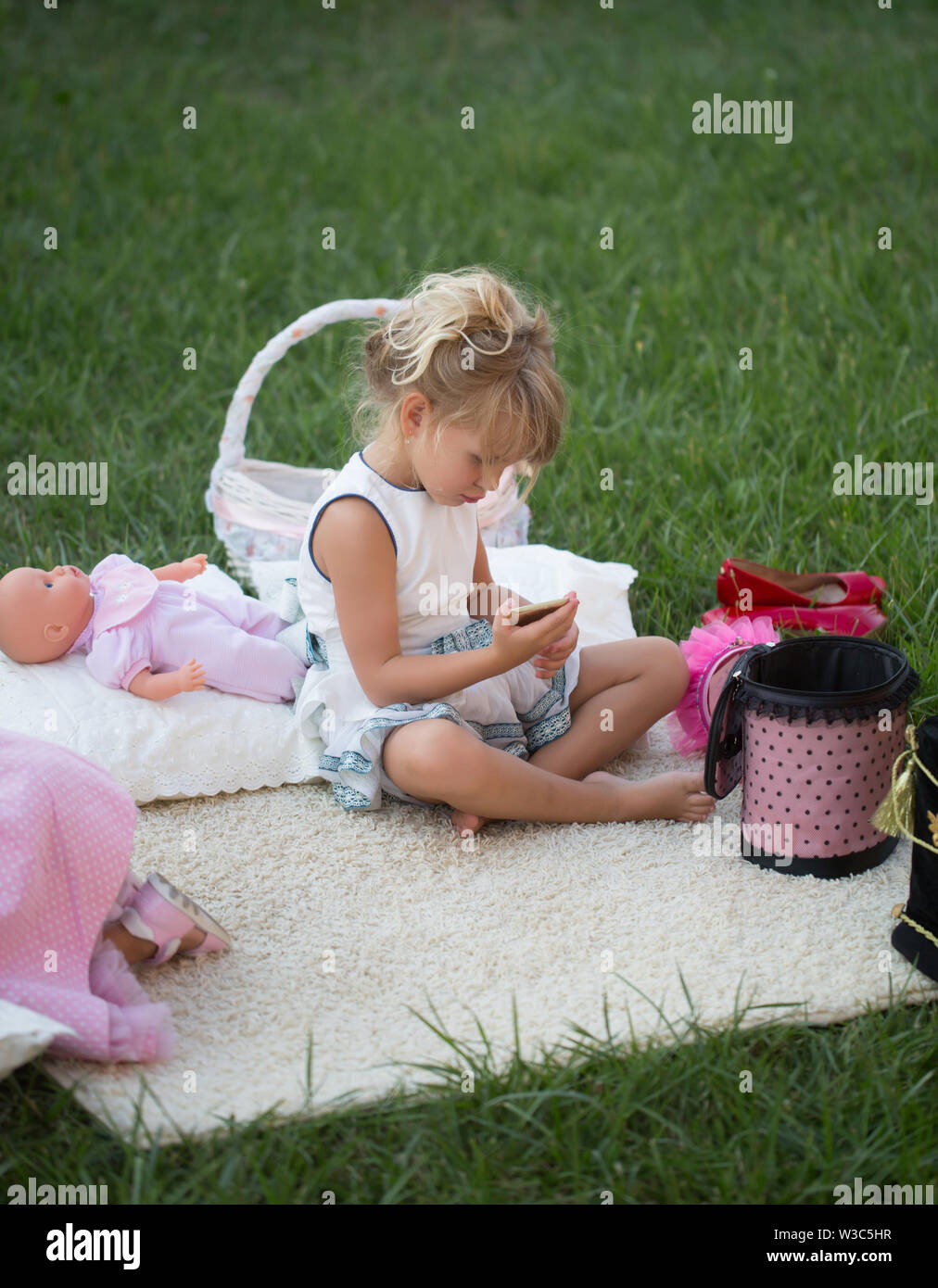 Girl with smartphone sit on cover on green grass. Child with mobile phone and doll on summer day. New technology, sms, communication, modern life. Vac - Stock Image