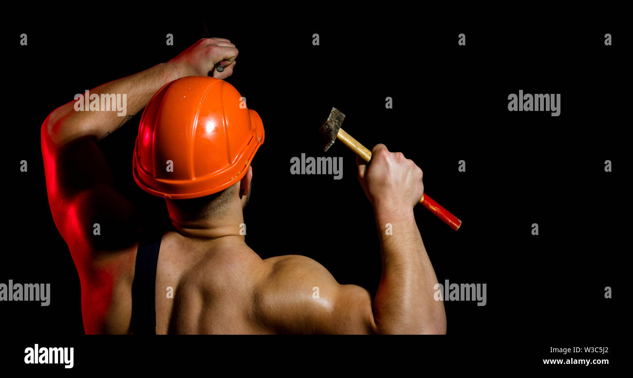 Currently under construction. Man work with hammer. Hard worker use muscular strength. Construction worker hammer a nail. Muscular man builder at work - Stock Image