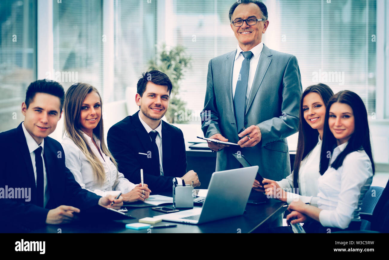 successful businessman and business team at a seminar in modern office. All business team smiling and everyone looks in the frame - Stock Image