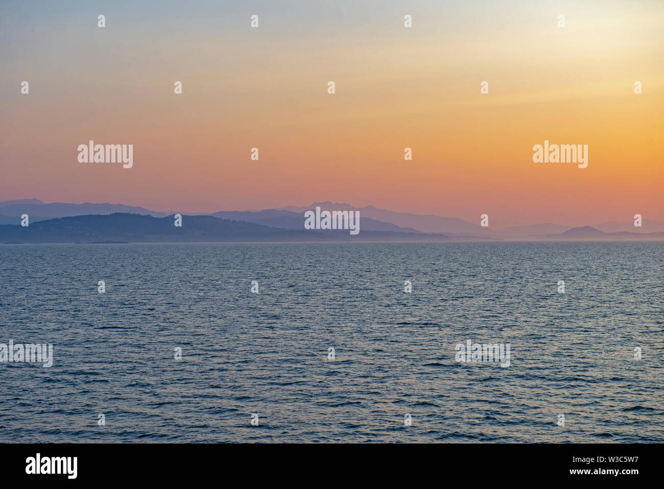 View of the Georgia Strait with the shore of Vancouver Island in the horizon, taken at sunset time in BC, Canada Stock Photo