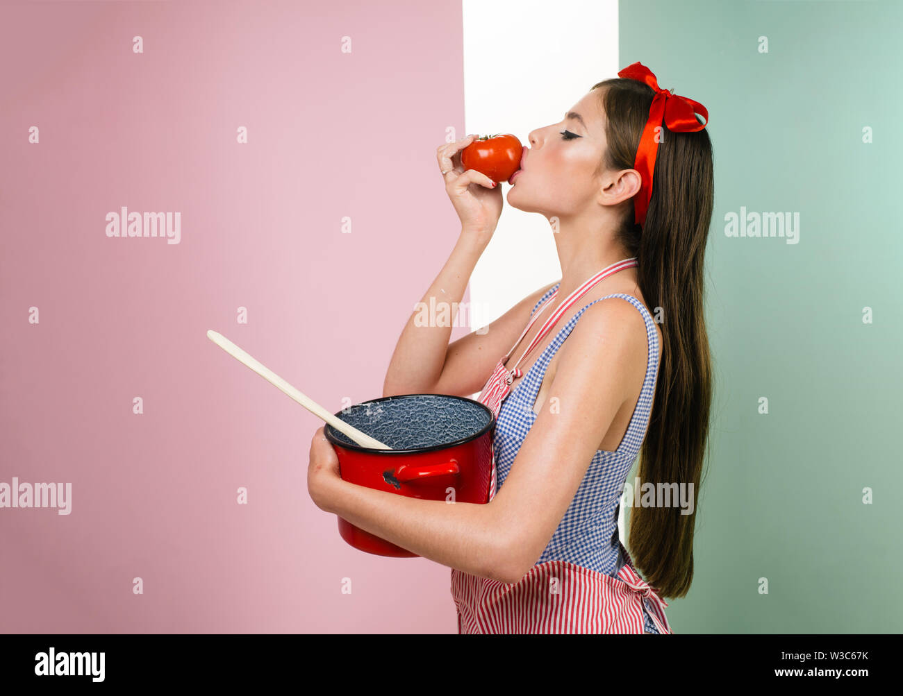 perfect housewife. pretty girl in vintage style. pinup girl with fashion hair. pin up woman with trendy makeup. retro woman cooking in kitchen. Only h - Stock Image