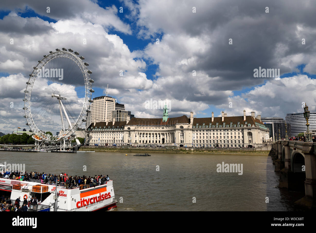London Eye on the River Thames with tourists on tour boats and Shrek's adventure and Sea Life Centre Aquarium from Westminster Bridge London England - Stock Image